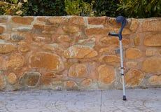Uma única muleta que descansa em uma parede de pedra que espera seu proprietário coxo foto de stock royalty free