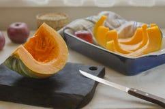 Uma abóbora alaranjado-verde encontra-se em uma placa de corte de madeira marrom e em um prato de cozimento cerâmico azul imagem de stock royalty free