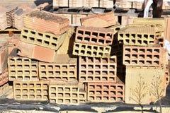 uma abundância de madeira da pálete de tijolos vermelhos empilhados velhos nas fileiras Atrás há a outra pilha dos tijolos vermel fotos de stock royalty free