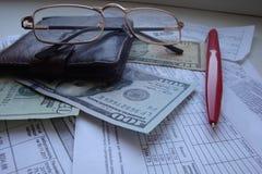 Uma ainda-vida com uma bolsa, uma pena, vidros, recibos, cálculos, dinheiro, dólares Imagem de Stock