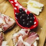 Uma ainda-vida das azeitonas, do queijo de cabra e da carne fumado caseiro em uma placa de madeira Fotografia de Stock Royalty Free