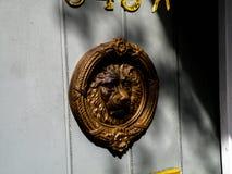 Uma aldrava de porta de bronze pendura na porta de uma casa no bairro francês de Nova Orleães fotos de stock royalty free