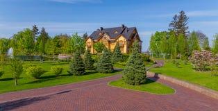 Uma aleia de passeio telhada que conduz a uma casa de madeira enorme com um telhado preto e a um lago decorativo na frente dele Fotos de Stock