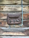Uma aleta elétrica oxidação-coberta velha na parede de uma vertente de madeira Os interruptores bondes da fiação e do plástico sã Fotos de Stock Royalty Free