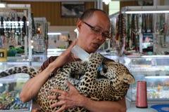 Uma alimentação do homem à criança do leopardo Foto de Stock