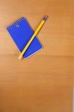 Uma almofada e um lápis de nota em uma mesa Imagem de Stock Royalty Free