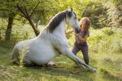 Uma amazona nova mostra um truque com seu cavalo treinado com o adestramento natural, introduzindo nos no mundo da equitação foto de stock