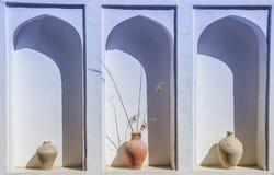 Uma ameia arqueada em uma parede branca com os vasos velhos da argila Pl envelhecido velho Imagens de Stock