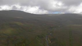 Uma antena revela a metragem inversa de uma inclinação gramínea da cimeira majestosa da montanha com um córrego, um céu azul e um video estoque