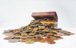 Uma arca do tesouro de madeira pequena que esteja estourando com moedas imagem de stock royalty free