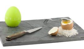 Uma ardósia cinzenta com um ovo fervido Foto de Stock Royalty Free