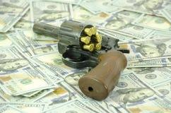 Uma arma com as balas da carga estabelecidas em dólares borrados fotografia de stock royalty free