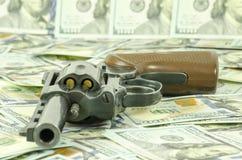 Uma arma com as balas da carga estabelecidas em d?lares borrados fotos de stock