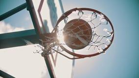 Uma aro de basquetebol Uma bola obtém no alvo Luz solar brilhante filme