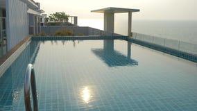 Uma associa??o luxuoso no telhado da casa com uma opini?o do mar No por do sol 4k, movimento lento, brilho solar na ?gua vídeos de arquivo