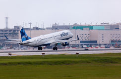 Uma aterrissagem de aviões de Embraer 190 das linhas aéreas de Jetblue Fotos de Stock Royalty Free