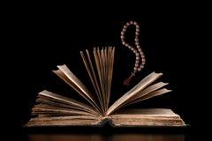 Uma Bíblia aberta com grânulos Fotografia de Stock Royalty Free