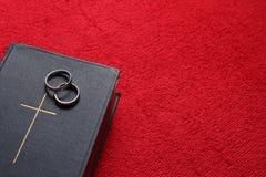 Uma Bíblia com anéis de casamento no fundo vermelho Fotos de Stock