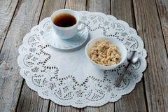 Uma bacia branca de farinha de aveia com café preto em um b de madeira natural Fotos de Stock Royalty Free