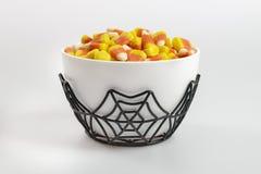 Uma bacia completamente de milho de doces de Dia das Bruxas em um fundo branco Foto de Stock