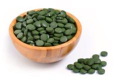 Uma bacia de madeira com o spirulina dos comprimidos e fim verdes da alga do chlorella acima no branco imagens de stock royalty free