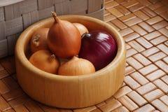 Uma bacia de madeira feita da madeira de bambu enchida com as cebolas Cozinha imagens de stock royalty free