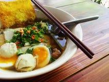 Uma bacia de sopa de macarronete com ovo e wonton friável Fotos de Stock