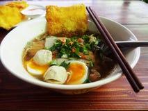 Uma bacia de sopa de macarronete com ovo e wonton friável Imagens de Stock