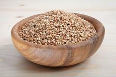 Uma bacia de trigo mourisco na superfície de madeira Imagem de Stock Royalty Free