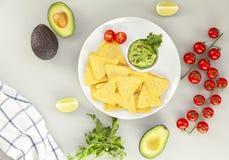 Uma bacia deliciosa de Guacamole ao lado dos ingredientes frescos em uma tabela com microplaquetas de tortilha Molho mexicano lat foto de stock royalty free