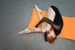 Uma bailarina descansa em um tapete para a ioga fotos de stock royalty free