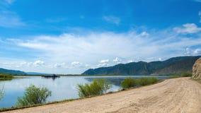 Uma balsa no rio de Selenga - a afluência a maior do Lago Baikal à proximidade da vila de Tataurovo Uma estrada do desvio avante imagem de stock