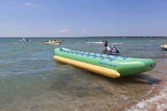 Uma banana inflável espera passageiros em uma atração da água na praia de Rodnichok na estância turística de Evpatoria, Crimeia fotografia de stock royalty free