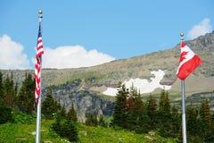 Uma bandeira americana e uma bandeira canadense no parque nacional de geleira Fotografia de Stock Royalty Free