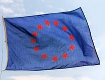 Uma bandeira azul com vermelho protagoniza em vibrações dos círculos no céu imagens de stock royalty free
