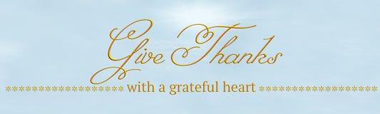 Uma bandeira com 'dá agradecimentos '& 'com um coração grato 'escrito no ouro foto de stock royalty free