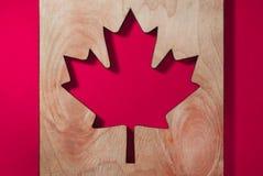 Uma bandeira de Canadá, uma folha de bordo cinzelou de uma árvore em um fundo brilhantemente vermelho imagens de stock royalty free