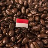 Uma bandeira de monaco colocada sobre feijões de café roasted fotos de stock