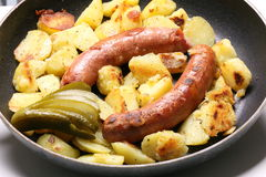 Uma bandeja com salsichas e batatas Imagens de Stock Royalty Free