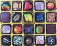 Uma bandeja do ouro de mão Crafted chocolates imagens de stock royalty free