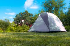 Uma barraca distribuída em um dia ensolarado em um gramado verde imagem de stock royalty free