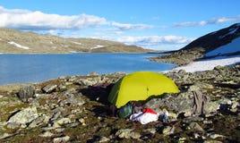 Uma barraca que stanging em picos e em geleira de montanha rochosa em Noruega Fotografia de Stock Royalty Free