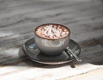 Uma bebida do cacau em uma caneca da argila em um fundo de madeira gasto Um copo da porcelana do café preto com marshmallows bran foto de stock