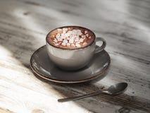 Uma bebida do cacau em uma caneca da argila em um fundo de madeira gasto Um copo da porcelana do café preto com marshmallows bran foto de stock royalty free