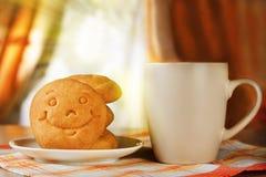 Uma bebida e um biscoito quentes com um sorriso Foto de Stock Royalty Free