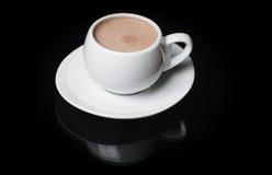 Uma bebida quente em um círculo branco em um fundo preto com reflexão Fotografia de Stock