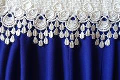 Uma beira do laço branco sobre a tela azul com dobras Imagem de Stock