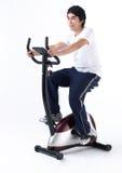 Uma bicicleta de ciclagem do homem em uma ginástica Imagem de Stock