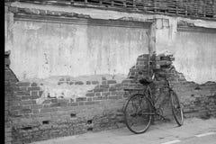 Uma bicicleta e uma parede de tijolo velhas Fotos de Stock