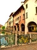 Uma bicicleta em uma ponte sobre um rio em Treviso Itália foto de stock royalty free